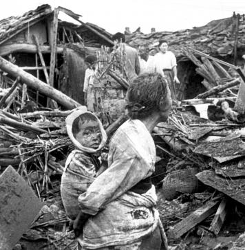 Una anciana y su nieto caminan entre los escombros de su casa tras un bombardeo de aviones norteamericanos sobre Pyongyang.